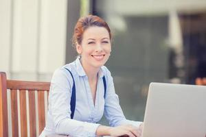 young happy smiling woman working on computer laptop outside outdoors