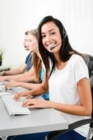 Alegre joven operador étnico femenino con auriculares llamando por teléfono con el cliente en una línea directa de servicio al cliente foto