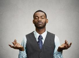 Young businessman meditating photo