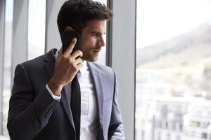 empresario haciendo llamadas telefónicas de pie junto a la ventana de la oficina