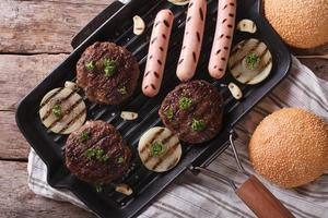 Burger and sausages on grill pan horizontal top view closeup
