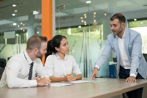 Business man standing and discussing issues with colleagues photo