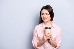 Portrait with empty place of dreamy thoughtful cute trendy woman having mug with warm tea in hands looking at copy space isolated on grey background