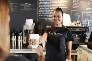 Barista femenino que sirve al cliente con café para llevar en la cafetería foto