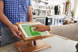 Customer using touch screen sales terminal at cafe, close up photo