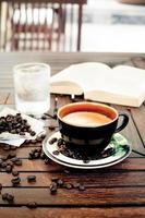 xícara de café, cappuccino com feijão e um livro.