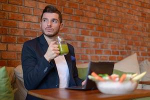 Businessman eating healthy in coffee shop photo
