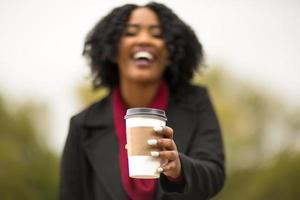 Woman handing you a cup of coffee. photo