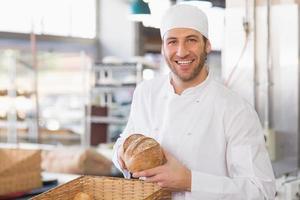 feliz panadero con barra de pan foto