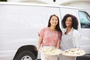 mujer entregando pizza de pie delante de la furgoneta foto