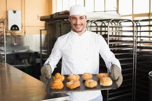 panadero mostrando bandeja de rollos foto