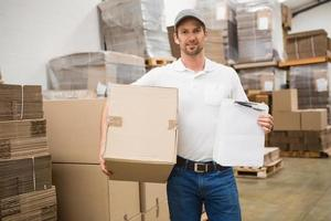 Delivery man with box and clipboard in warehouse photo