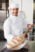 feliz panadero sacando pan fresco foto