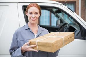 Delivery driver smiling at camera by her van holding parcel photo