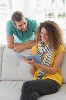 mujer sonriente en el sofá mostrando a su compañero de trabajo su cuaderno foto