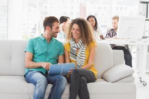 diseñadores sonrientes trabajando juntos en el sofá foto