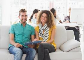 diseñadores sonrientes trabajando juntos en el sofá mirando a la cámara foto