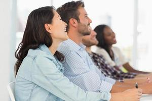 sonriente equipo de jóvenes diseñadores escuchando en reunión foto