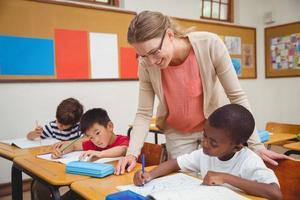 Linda maestra ayudando a un alumno en el aula foto