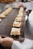 bouchent boulanger tenant le plateau de pâte crue