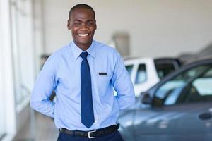 Vendedor afroamericano que trabaja en la sala de exposición de vehículos foto