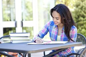 studente etnico che scrive e studia con molti libri