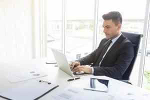 Apuesto hombre de negocios trabajando en escritorio con ordenador portátil y papel gráfico en la oficina. Empresario profesional y concepto de tecnología. foto