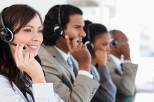 Smiling call centre employee working while accompanied by her team