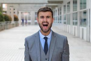 Businessman screaming in office space photo
