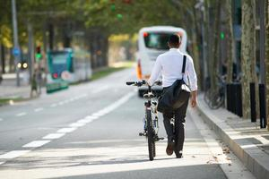 Businessman Walking with Bike in Street After Work