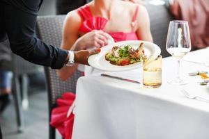 Camarero llevando un plato con ensalada en la boda. foto