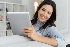 mulher jovem e bonita usando seu tablet digital em casa.