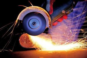 trabajador cortar metal con molinillo foto