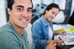 Smiling graphic designers at desk