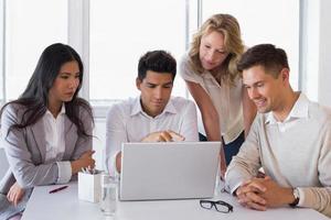 equipo de negocios informal sonriente que tiene una reunión usando la computadora portátil foto