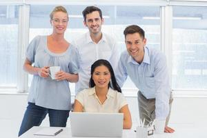 Casual business team using laptop together at desk