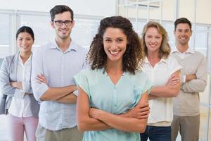 equipo de negocios informal sonriendo a la cámara con los brazos cruzados foto