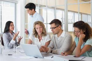 equipo informal de negocios que tiene una reunión usando una computadora portátil foto