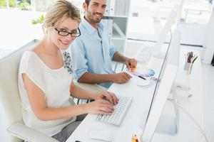Casual young couple working on computers photo