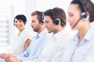 Business colleagues with headsets in a row photo