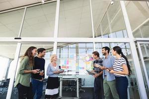 Smiling business colleagues standing against glass wall photo