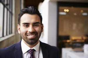 Young Hispanic businessman smiling to camera photo