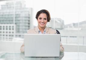 empresária feliz usando o laptop na mesa dela