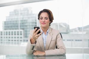 empresária sorrindo para seu smartphone