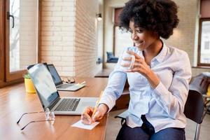 Empresaria con taza de café en la oficina foto