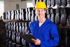 Botas de goma trabajador de almacén de fábrica con portapapeles foto