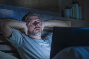 attractive tired and stressed workaholic man working late night exhausted on bed busy with laptop computer feeling sleepy and overworked in business project deadline stress concept photo