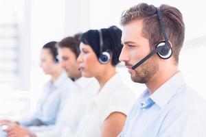 collègues de travail avec des casques d'écoute dans une rangée