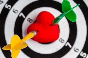 Black white target with darts in heart love as bullseye photo