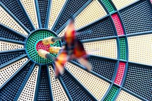 Blurred darts stuck in bulls-eye